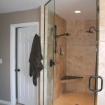 Master bath shower after with contemporary oil rubbed bronze and Travertine tile.